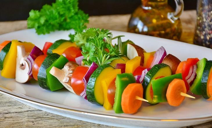 Några grillspett ligger på en tallrik. På spetten sitter det massa olika bitar av grönsaker, som morötter, paprika, svamp, lök och zucchini.