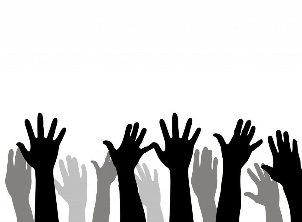 Många händer uppsträckta i luften.