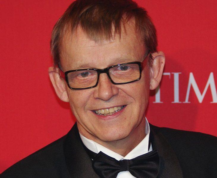 Hans Rosling tittar in i kameran. Han ser ut att vara i övre medelåldern. Han har kavaj och fluga på sig. Han har glasögon och ganska tunt kort hår som ligger kammat framåt. Hans tänder är gula och han har ganska stora öron.