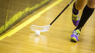 Fötter med sportskor springer över ett trägolv. Bredvid fötterna syns en bandyklubba som föser en bandyboll framför sig.
