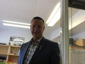 En person med kavaj och skjorta står på ett kontor.