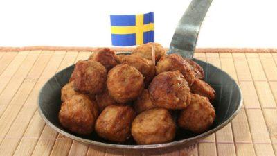 En liten stekpanna med en hög av köttbullar i. Istucket bland köttbullarna är en liten svensk flagga.