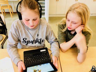 Två skolbarn sitter vid ett skrivbord med en dator. Ena barnet har på sig hörlurar.