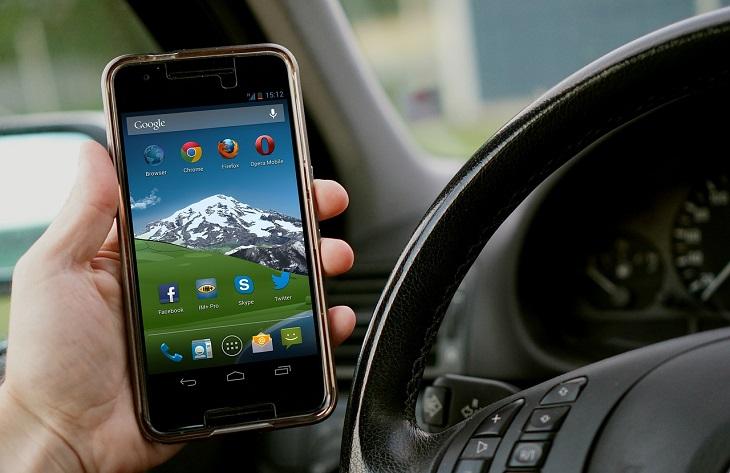 En hand håller i en mobil bredvid en ratt i en bil.