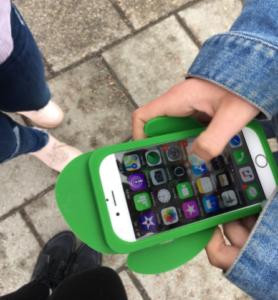 En hand håller i en smartphone med grönt mobilskal i plast. I bakgrunden syns markens stenplattor och två personers skor.