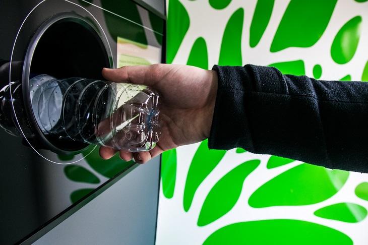 En arm sträcker fram en plastflaska mot en pantmaskin. Flaskan försvinner halvvägs in i ett hål i maskinen.