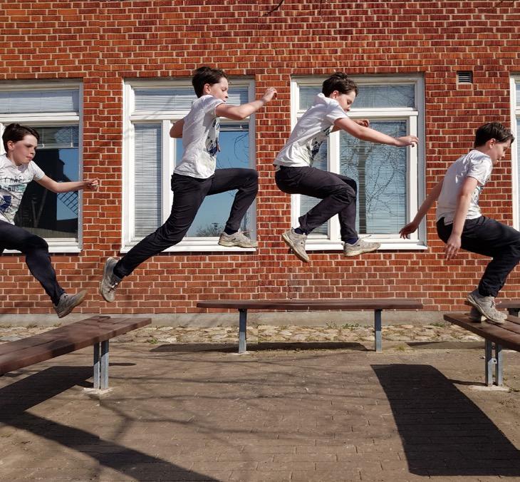 En skolelev hoppar mellan två bänkar. Vi ser honom på fyra olika ställen i luften.