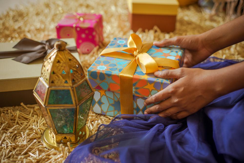 Ett par händer håller en present. Bredvid ligger fler presenter och det står en färgglad och guldig ljuslykta bredvid.