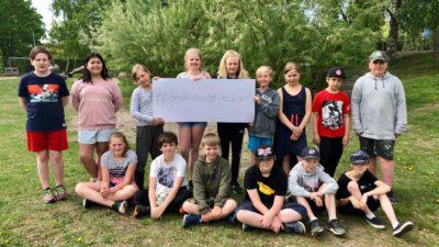 15 skolbarn på en gräsmatta håller i en skylt med texten #snällanätveckan.