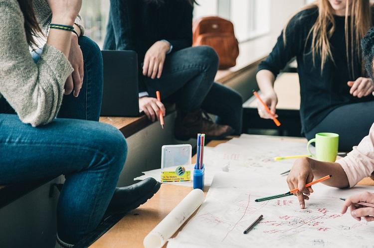 Några sitter runt ett bord och ritar och skriver på ett stort papper. Några sitter i fönstret, några på stolar. Det ligger pennor och står muggar på många ställen på bordet.