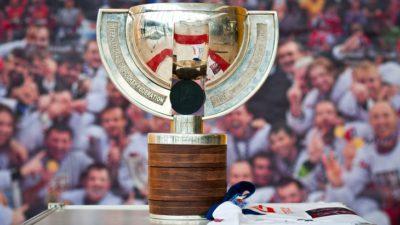 En stor guldig pokal står på ett bort. Pokalen har en fot av trä, en stor skål av guld. Från foten och upp runt var sin sida av skålen går två remsor av metal ut. På remsorna står det text.