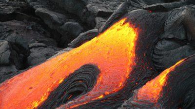 Eldig lava som rinner med svart stelnad lava runt omkring