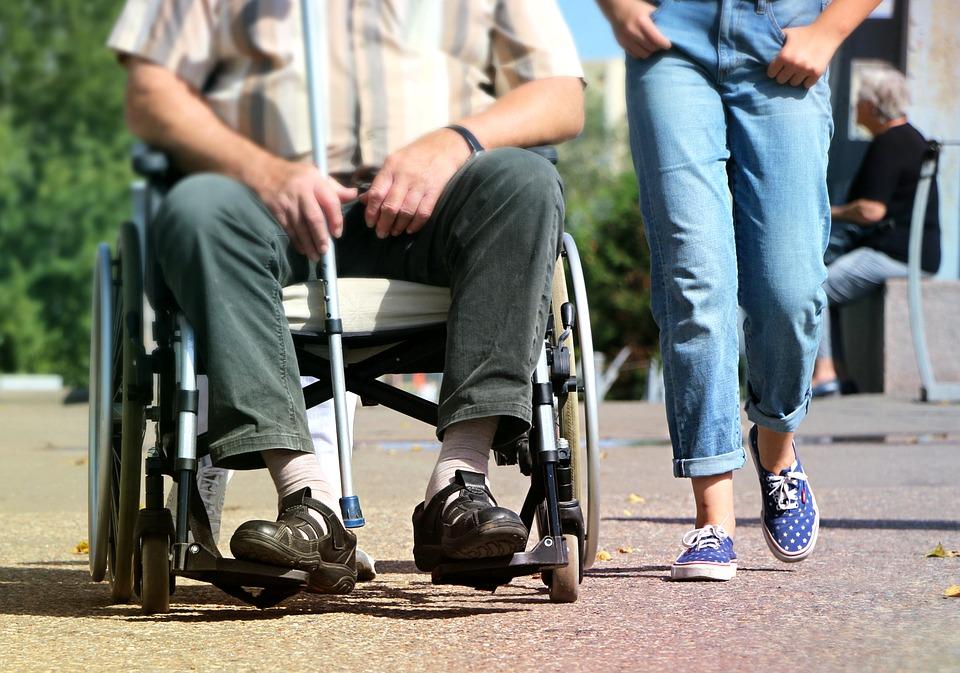 En person sitter i rullstol och håller i en käpp med en stödperson i blå jeans som går bredvid