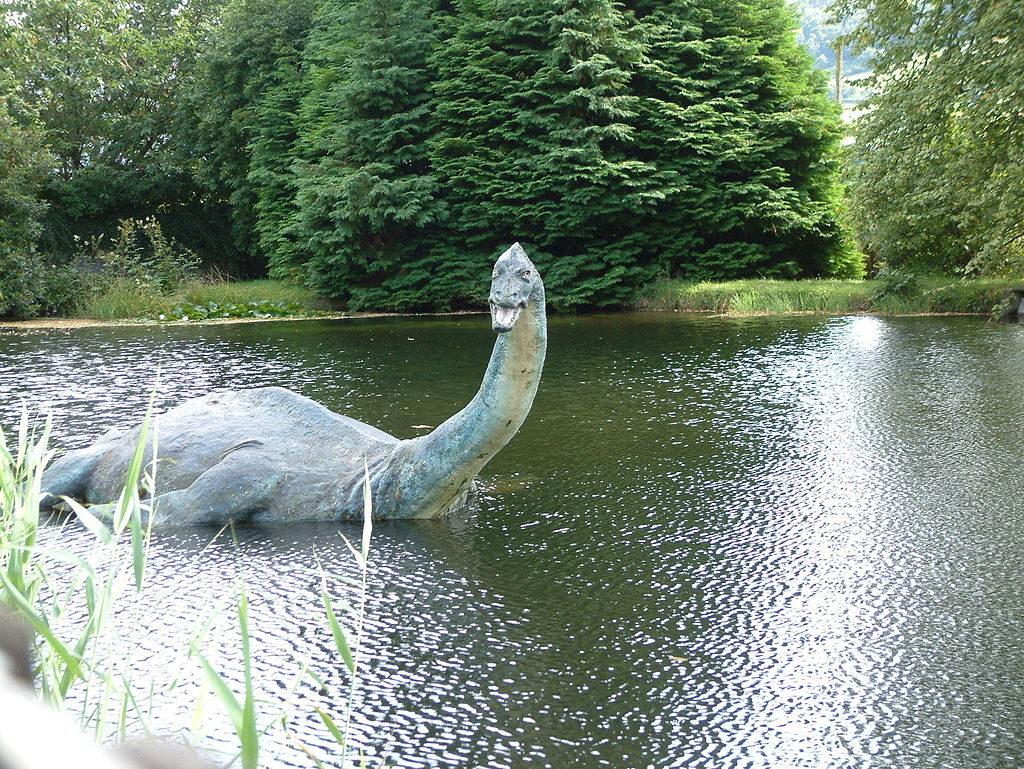 En sjö med träd vid sjökanten. I sjön ligger en stor staty. Statyn har avlång men stor kropp, lång halv, litet huvud och fenor. Den öppnar munnen och gapar mot oss.
