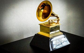 Ett pris står på en bänk. På den fyrkantigafoten sitter en silverplatta med text. På foten står en liten gramofon i guld.