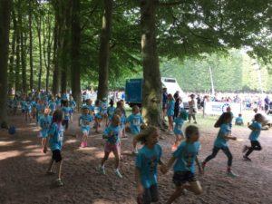 Barn med blåa tröjor springer på grusgången.