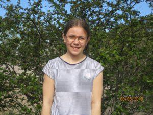 Julia står framför en buske.