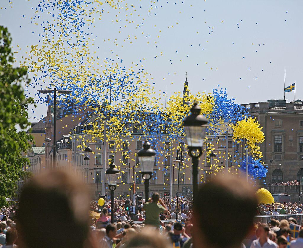 Många människor står på gator och torg. Ovanför dem flyger ballonger i stora sjok.