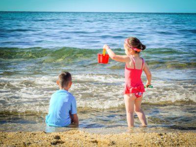 Två barn som leker vid en strand.