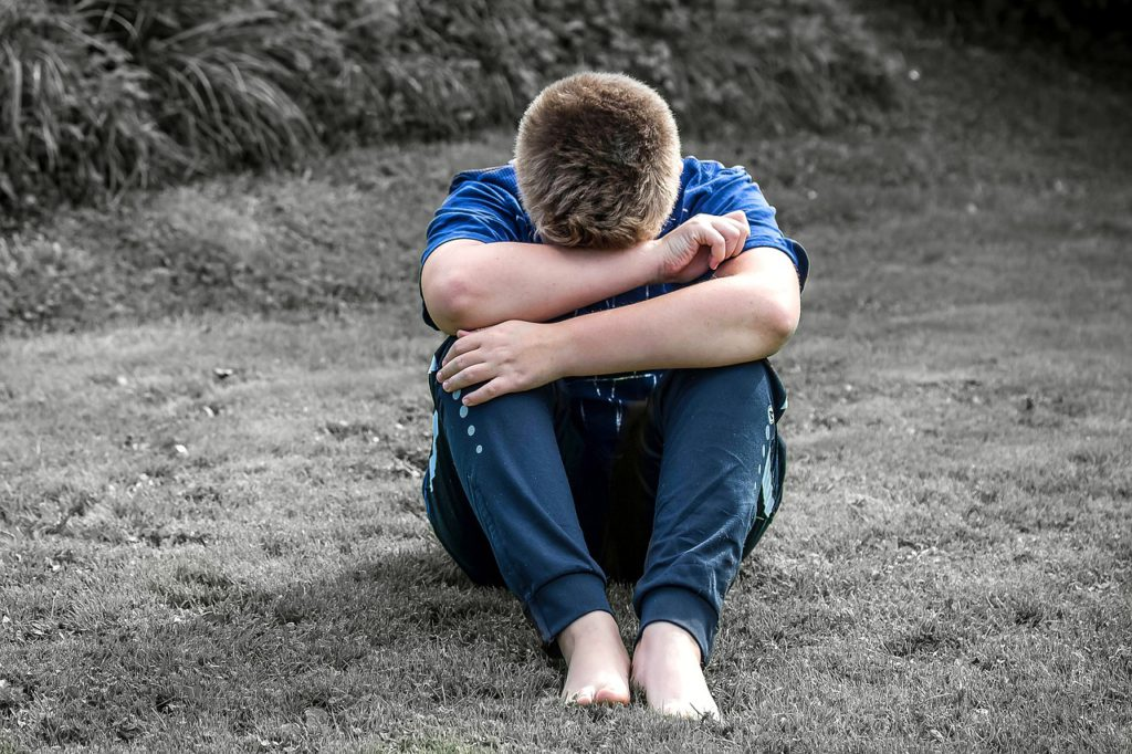 Ett barn sitter på en gräsmatta. Han har dragit upp knäna och lagt armarna på dem. Han gömmer huvudet i armarna. Det ser ut som att han gråter.