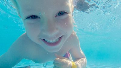 En närporträtt av ett barn under vattnet som ler in i kameran.
