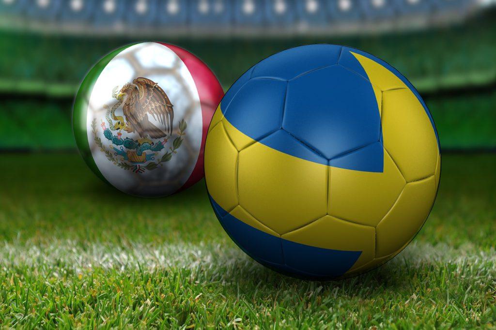 Två fotbollar ligger på en fotbollsplan. Den närmste bollen är helt blå med ett gult kors hela vägen runt. Den andra bollen är grön, vit och rödrandig. På det vita fältet syns en stor örn som sotter på en kaktus.