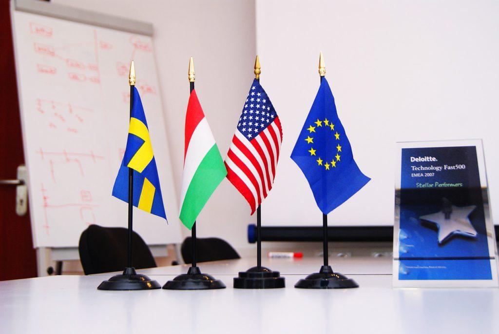 Fyra små flaggor sitter på varsin pinne och står på ett bord. Det är en svensk flagga, en italiensk, en amerikansk och EU:s flagga.