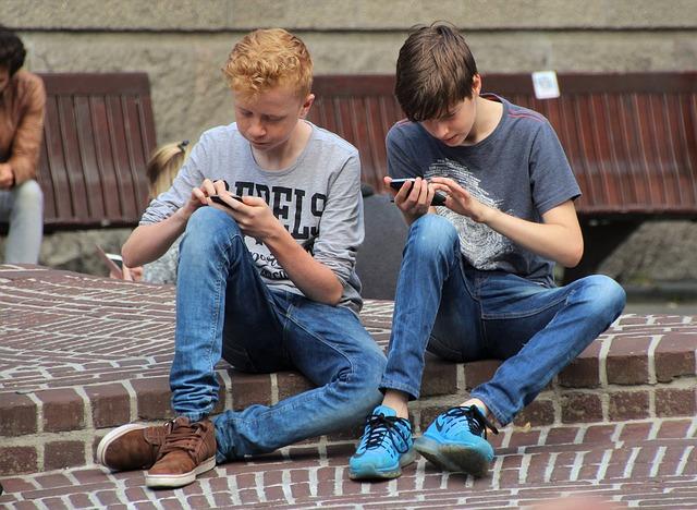 Två barn sitter med sina smartphones på marken.