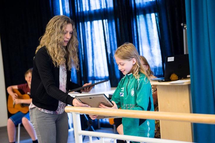 En vuxen håller i två inramade diplom. Barnet tar emot det ena. De är i ett stort rum med stora fönster med fördragna blåa gardiner.