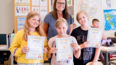 Chefredaktör Marie Hillbom står bakom Astrid, Emelie och Viktor som visar upp sina diplom. De står i ett klassrum.