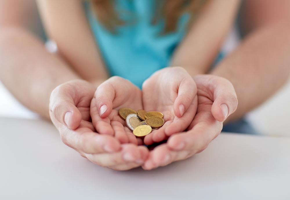 En vuxen håller fram sina händer som en skål. I händer har ett barn lagt sina händer. I barnets händer ligger det flera mynt.