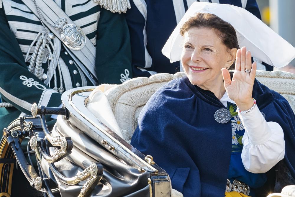 Drottningen sitter i en öppen vagn och vinkar och ler. Hon har en vit duk på huvudet och en blå mantel som ligger över axlarna.