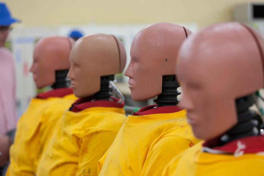 Flera stora dockor sitter i rad. De har huvuden med ansikten som liknar människor, men utan ögon. Nacken är en svart fjäder. De har gula rockar på sig.