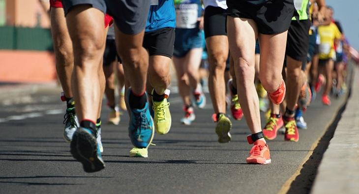 Många ben som springer. De flesta har färgglada springskor på sig. De springer på asfalt och solen skiner.