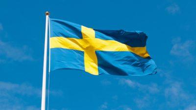 En svensk flagga vajar i vinden på en flaggstång. Solen lyser på flaggan och himlen är blå bakom.