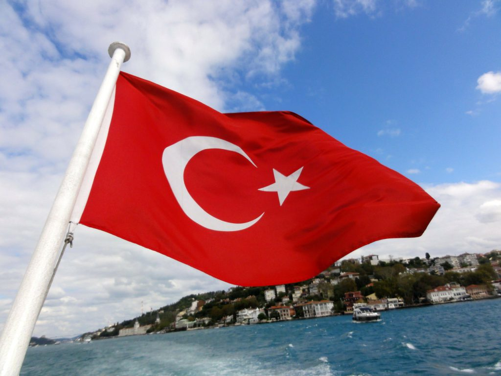 Turkiets flagga viftar i vinden över vatten. Det ser ut som att den sitter längst bak på en båt. Flaggan är röd med en vit halvmåne och en vit stjärna.