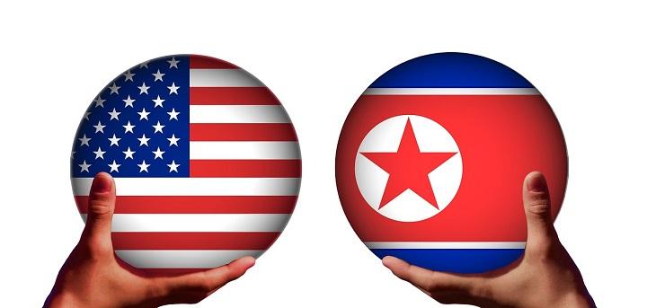 Två händer håller i varsin kula. Den ena kulan har USA:s flagga, med röda och vita ränder och vita stjärnor på en blå bakgrund i ena hörnet. Den andra kulan har Nordkoreas flagga. Den har en bred röd rand i mitten, blåa kanter och en vit cirkel med en röd stjärna i.