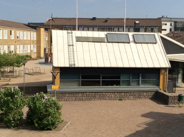 Bild på skolgård med buskar, hus och grus.