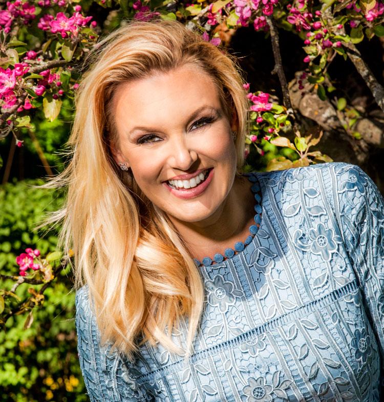 Sanna Nielsen ler stort och tittar in i kameran. Hon har blont hår och en blå klänning på sig. I bakgrunden syns buskar och ett träd med rosa blommor.