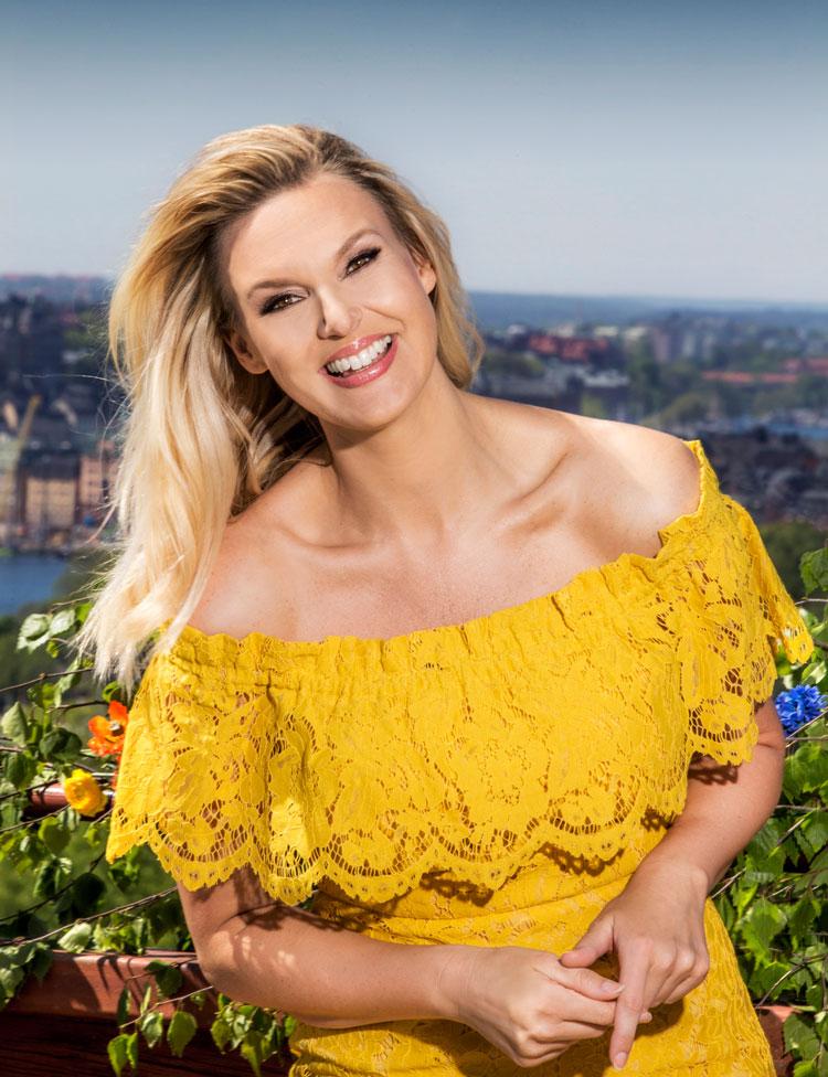 Sanna Nielsen ler stort och tittar in i kameran. Hon har blont hår och en gul blus på sig. I bakgrunden syns Stockholm stad.