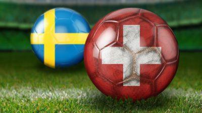 två fotbollar en med sveriges flagga och en med schweiz