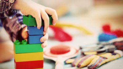 Ett barn som leker med klossar med andra leksaker i bakgrunden