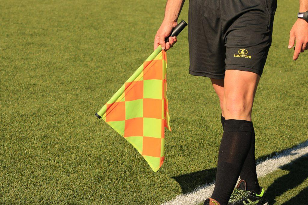 En fotbollsdomare meden flagga.