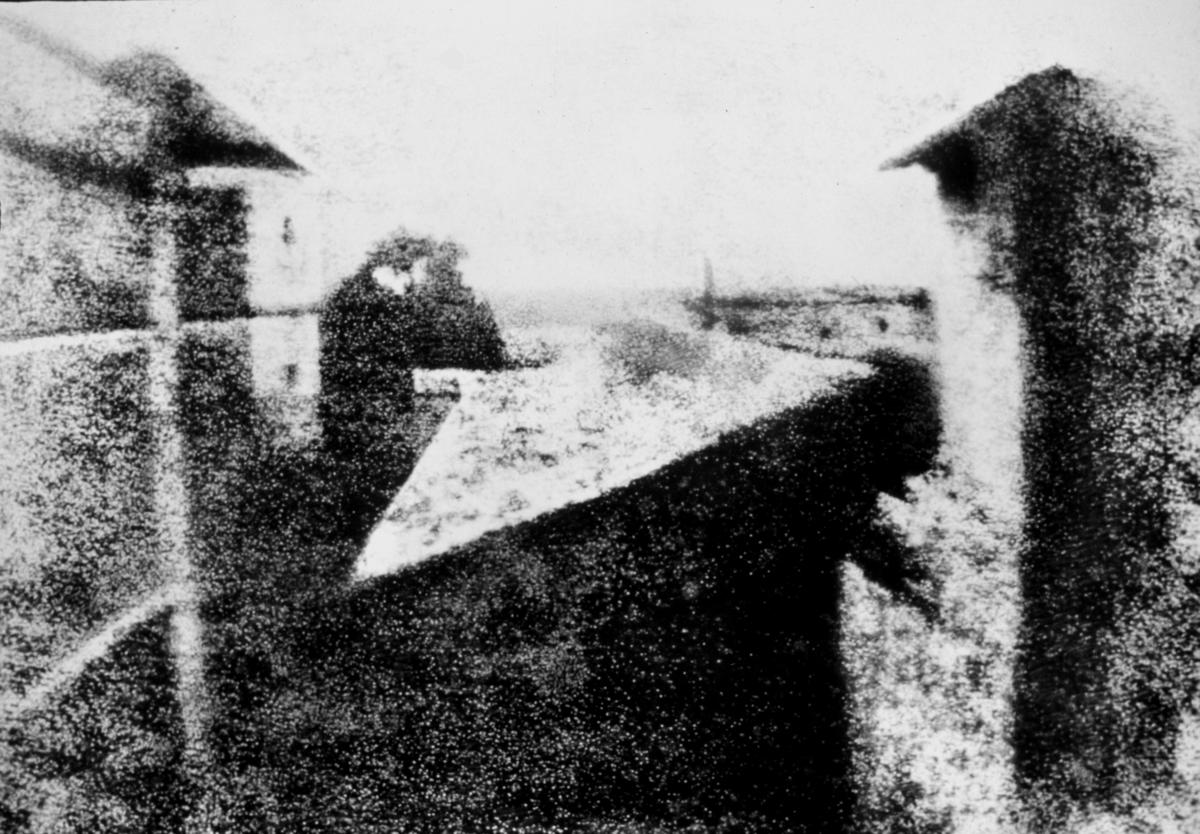 En svartvit lite suddig bild på hus,. Den första bilden som fångats på plåt