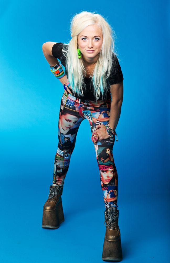 Amelie Nörgaard står mot en blå bakgrund. Hon lutar sig framåt och tittar in i kameran. Hon har långt blont hår, svart tröja, färgglada byxor och mörkgrå platåskor på sig.