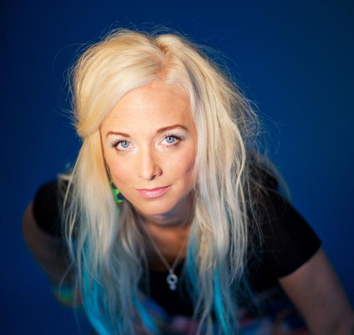 Amelie Nörgaard står mot en blå bakgrund. Hon lutar sig fram och tittar in i kameran.
