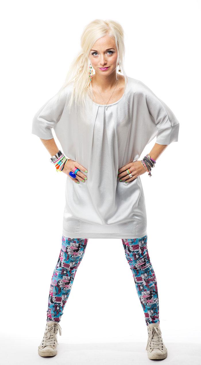 Amelie står med händerna på höfterna. Hon har blont hår i en tofs, stor ljugrå blus, färgglada leggins och vita sneakers på sig.