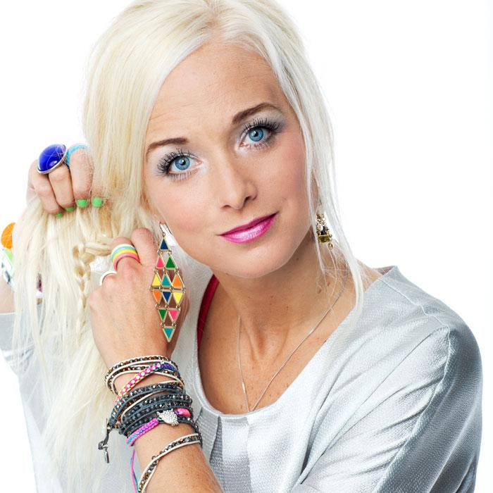 Amelie håller i sitt långa blonda hår. Hon har på sig en ljusgrå blus, färgglada örhängen och armband.