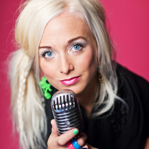 Amelie Nörgaard håller i en mikrofon mot en rosa bakgrund.
