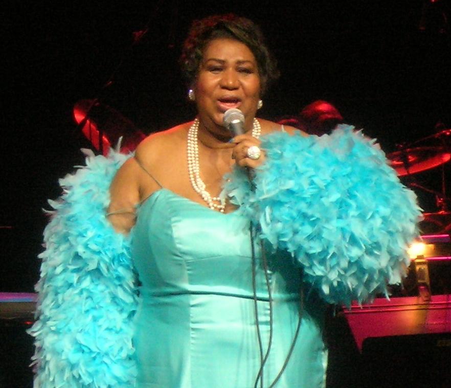 Aretha Franklin i en turkod klänning på scen.